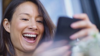 Attractive woman laughing as she sees something on her phone