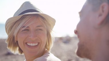Attractive female glances and smiles at her charming boyfriend on the beach