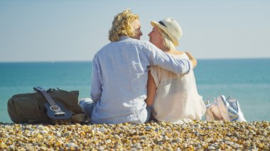 Young couple on a beach about to kiss on a bright sunny day