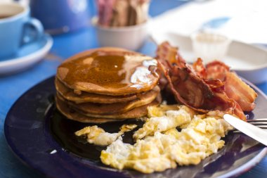 Pancakes, bacon and eggs with dripping maple syrup on a breakfast plate on a table