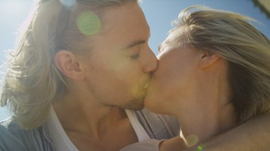 Young couple share a kiss in lovely sunlight