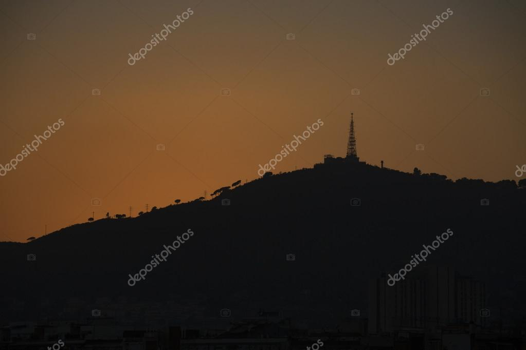 Warm glow of sunset creating a silhouette on a hilltop in the distance