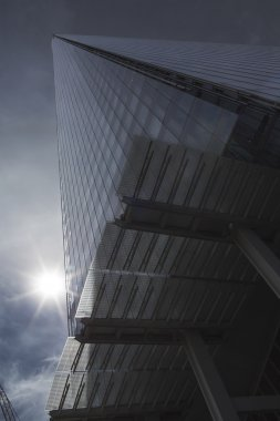 LONDON, UK - JULY 3, 2015 - The Shard, an epic building that dominates the London Skyline with it's distinctive architectural design, as seen from below with sun flare