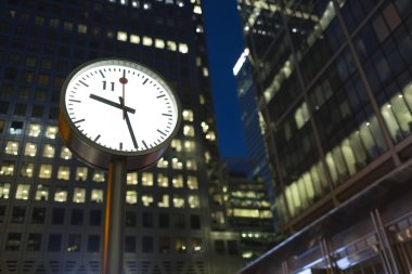 LONDON, UK - AUGUST 3, 2015 - Canary Wharf clock in the evening as office lights remain on in the background. Central finance district in London