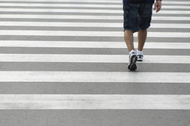 Legs of a man wearing shorts and sneakers walking across a zebra crossing