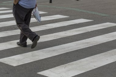 Legs of a man crossing a zebra crossing