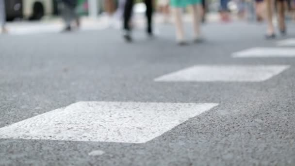 Feet of busy pedestrians crossing the street at a busy intersection
