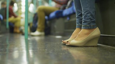 Feet of a woman in shoes sitting on a subway train carriage with other unseen commuters