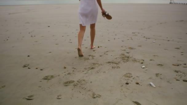 žena chodí po prázdné písčité pláži