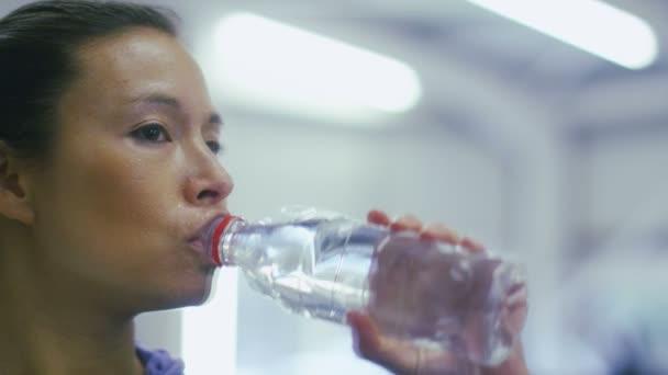 Atraktivní žena pije balenou vodu v tělocvičně