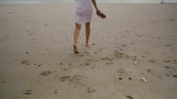 nő sétál végig az üres homokos strand