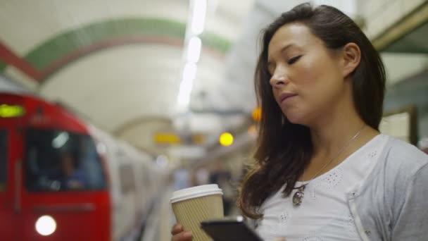 žena v podzemní metro a kontrolu její telefon