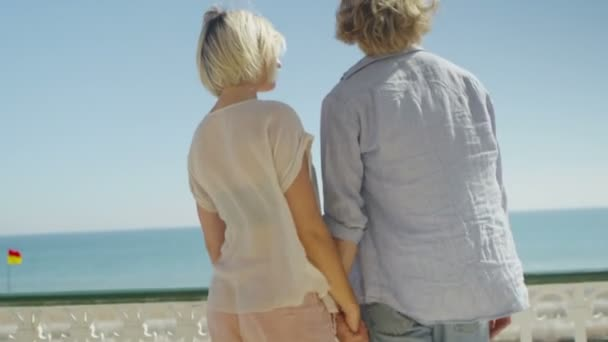 couple holding hands embrace and look out to sea
