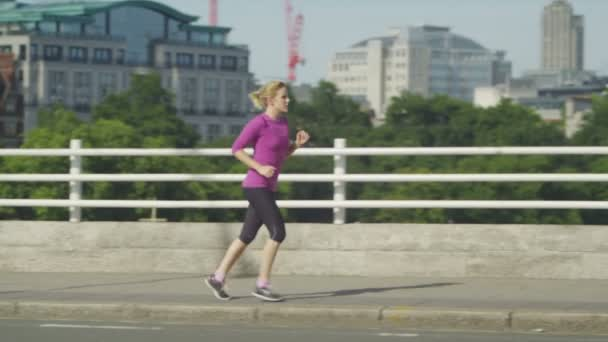 Woman running across a bridge in the daytime for exercise
