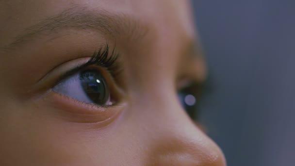Oči dítěte jako je zabraný do něčeho na obrazovce