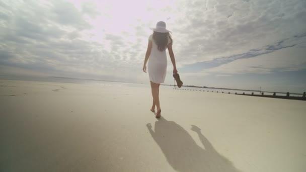 woman walks along the sand on the beach