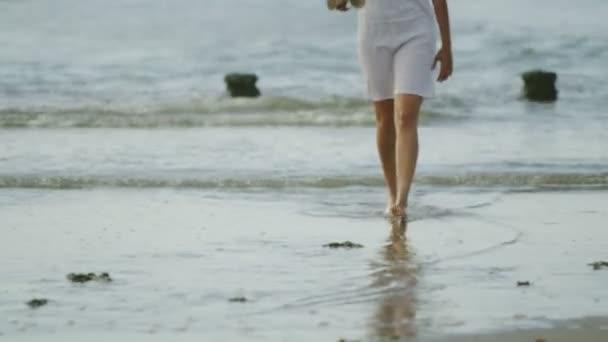 žena chodí po pláži pobřeží