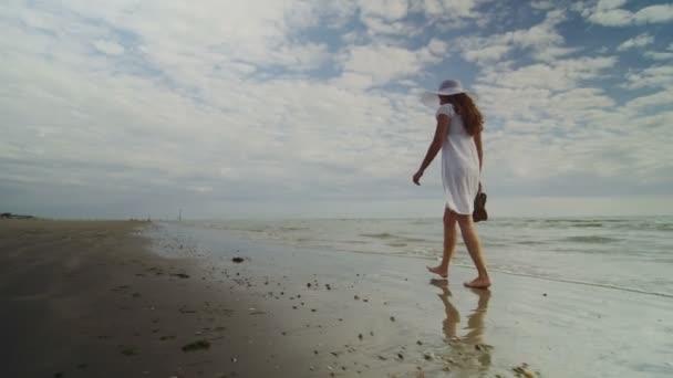 žena chůze podél surf pláž