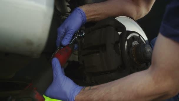 Mechanik odšroubujete díly, zatímco změna brzdového kotouče na auto