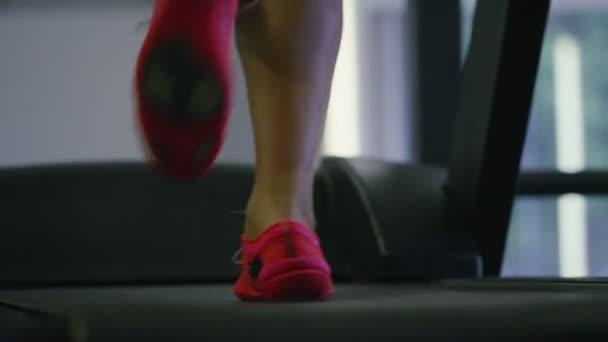 mladá žena běží na běžeckém pásu
