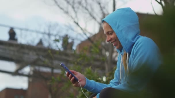 Woman using a cell phone outdoors and smiling