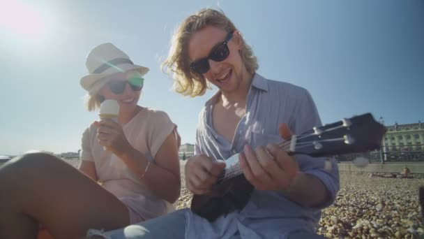 couple on a beach having fun with a ukulele and ice cream
