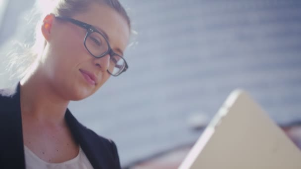 businesswoman in glasses using a tablet outdoors