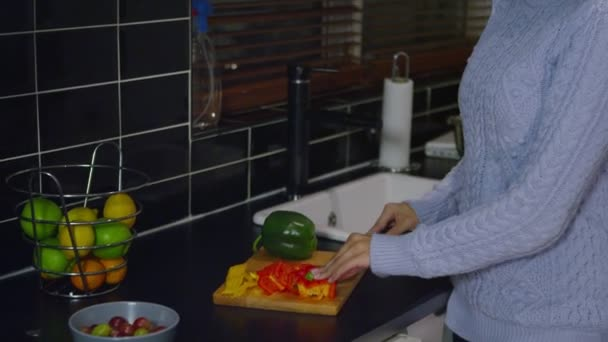 Woman cuts peppers in a kitchen and smiles