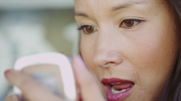 woman applying her lipstick in a small mirror