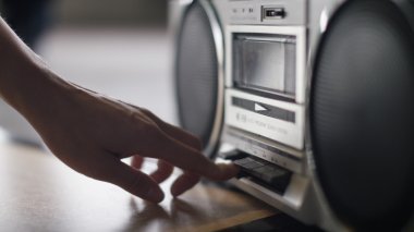Hand of a female presses play on an old cassette stereo system