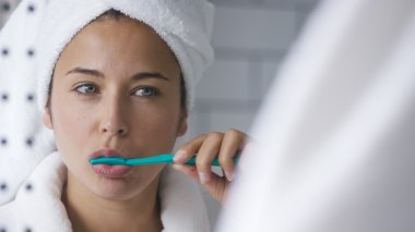 Young woman in the bathroom brushing her teeth in front of the mirror