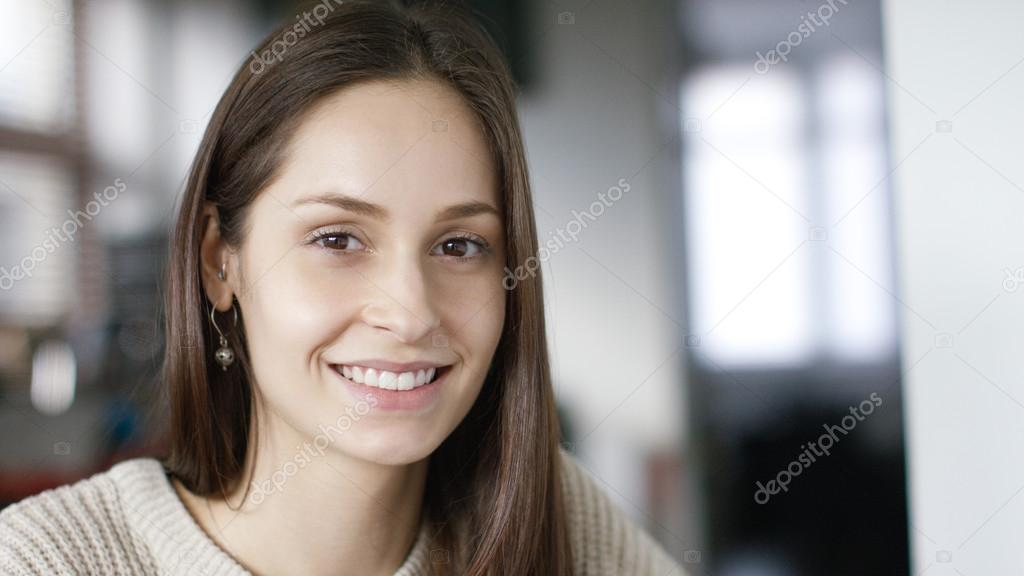 Portrait of an attractive young woman smiling to camera in home surroundings