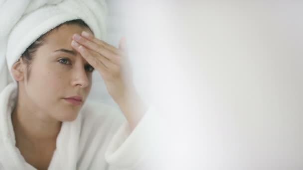 žena použití hydratační na její tvář v zrcadle