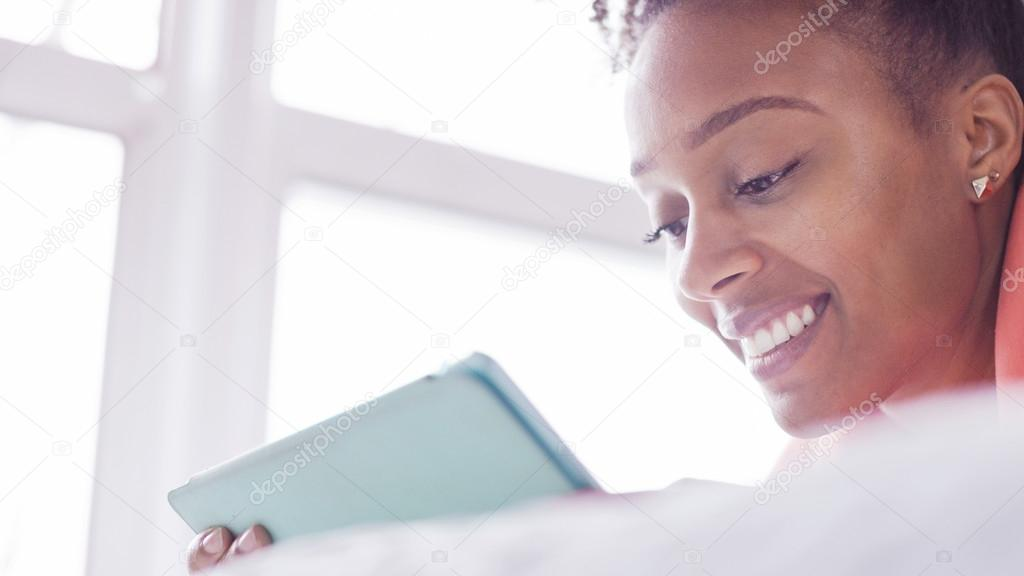 Close up of attractive woman reading a digital tablet