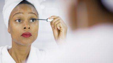 Attractive young woman applying mascara to her lashes in the mirror