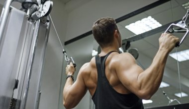 Muscular man working out on a cable machine
