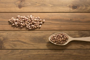 Some speckled beans and a spoon on a wooden table