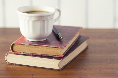 Coffee cup and Fountain Pen  on a pile of books