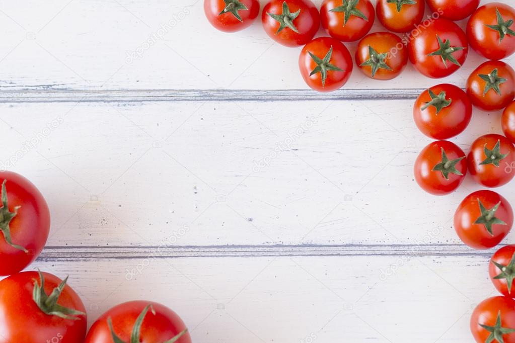 Several tomatoes on a white wooden table