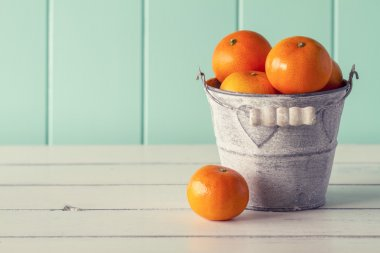 Bucket full of oranges on a white wooden table with a robin egg blue background