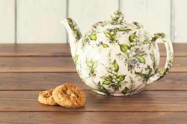 A teapot and two german cookies on a wooden table with a white background. Vintage style.. Five o'clock. Tea time. Vintage style.