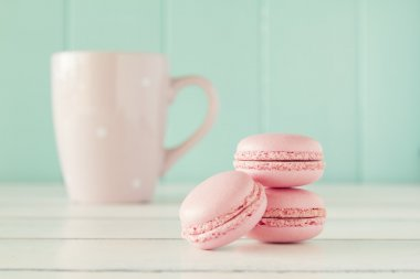 Some macarons and a pink mug on a white wooden table with a robin egg blue background. Vintage Style.