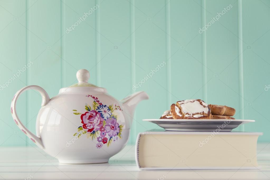 Un vaso de agua y unas galletas en una placa sobre un libro blanco ...