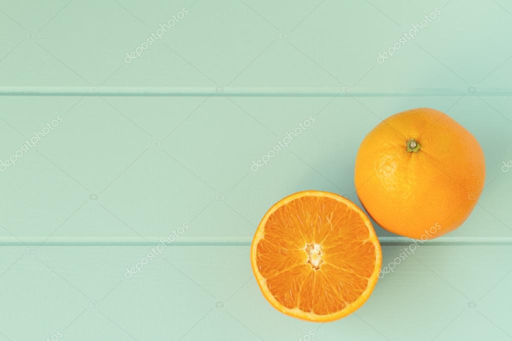 Two oranges on a robin egg blue wooden table. Vintage Style.