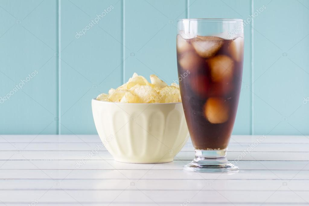 Potato chips in a bowl and a glass of cola on a white wooden table with a robin egg blue background. Vintage Style.