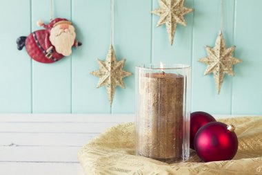 A candle and two red christmas balls. On the background Santa Claus flies between gold stars on a turquoise wooden wainscot. Christmas vintage style.