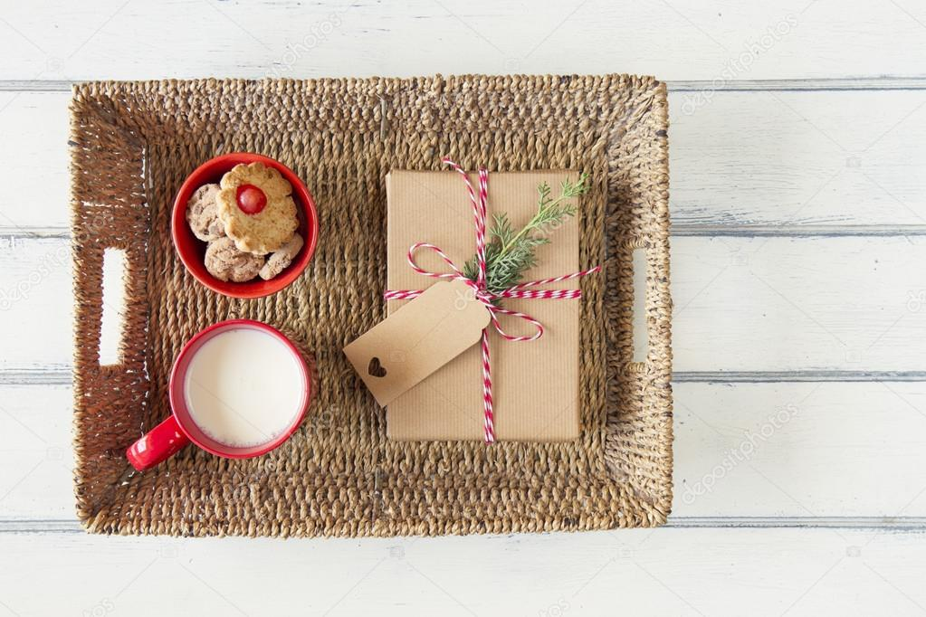 A paper parcel wrapped tied with a tag, a red bowl with shortbreads and a milk mug. A christmas gift box wrapped with paper kraft and tied with red & white baker's twine. Vintage Style.