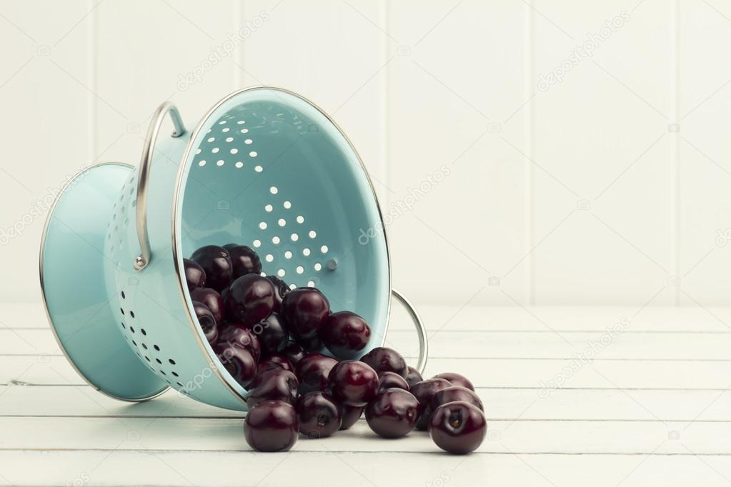 Some cherries in a turquoise strainer