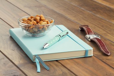 A cup of honey roasted peanuts on a wooden table, a turquoise notebook, a ballpoint and a wristwatch