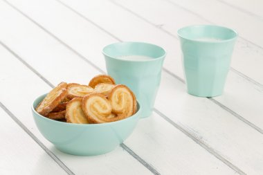 Some puff pastry heart cookies in a mint bowl and two milk glasses on a white wooden table